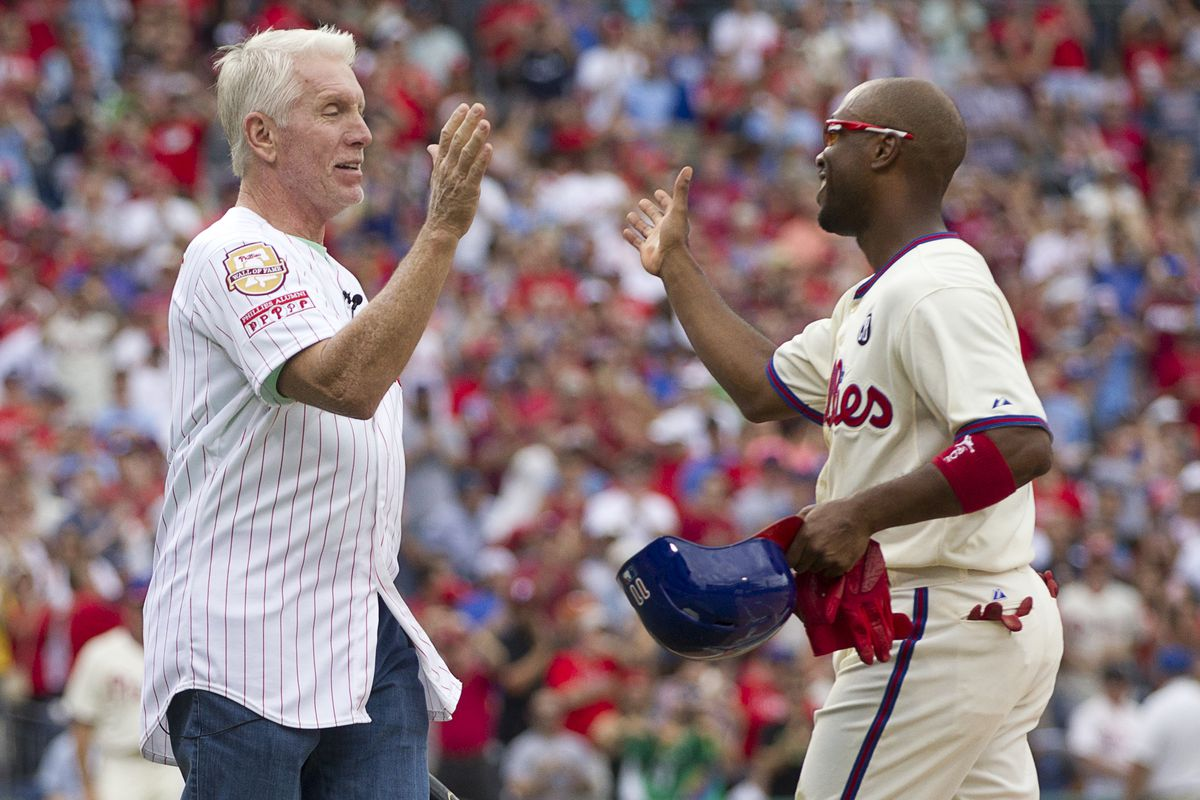 Shortstop Jimmy Rollins of the Philadelphia Phillies hits a single in the bottom of the fifth inning against the Chicago Cubs and is congratulated by former Phillies third baseman Mike Schmidt on June 14, 2014 at Citizens Bank Park in Philadelphia, Pennsylvania. This single makes Jimmy Rollins the all-time Phillies career hit leader with 2,235 hits.