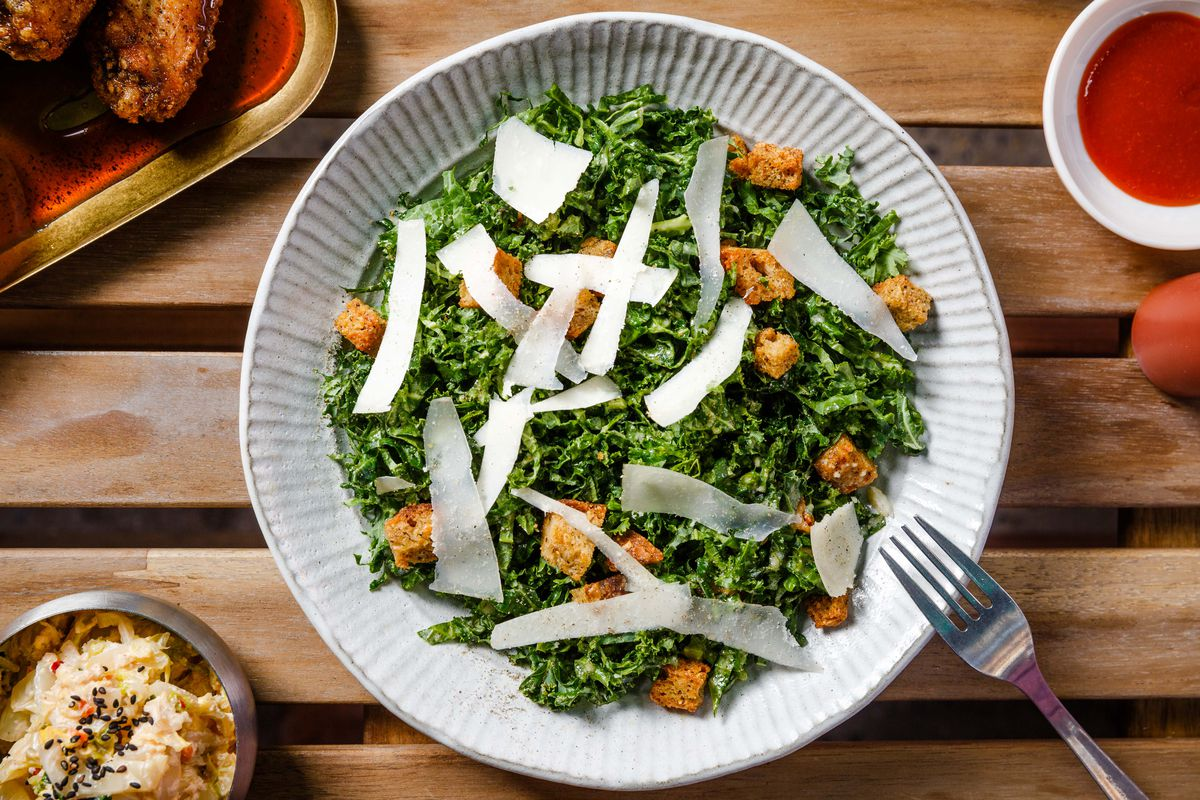 Croutons and parmesan slices sit atop a bed of verdant kale leaves in this Caesar salad preparation, shot from above over a wooden table