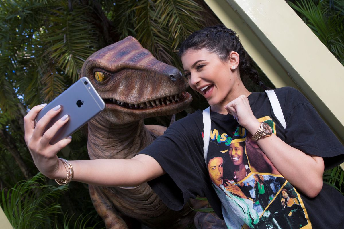 Kylie Jenner takes a selfie with a velociraptor.