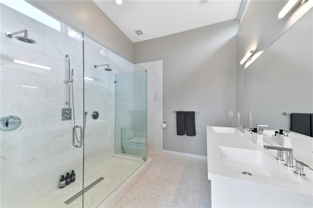 A large white master bathroom with glass surrounds.