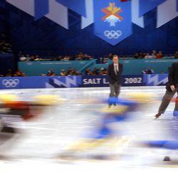 Judges watch racers take a corner in the men's 1,000 meter short-track speedskating heats at the Salt Lake Ice Center on Feb. 13, 2002.