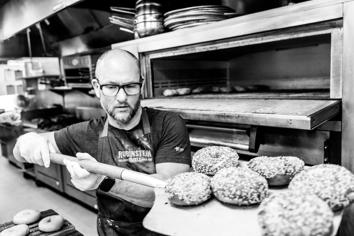 Bagel maker Andrew Rubinstein taking bagels out of the oven