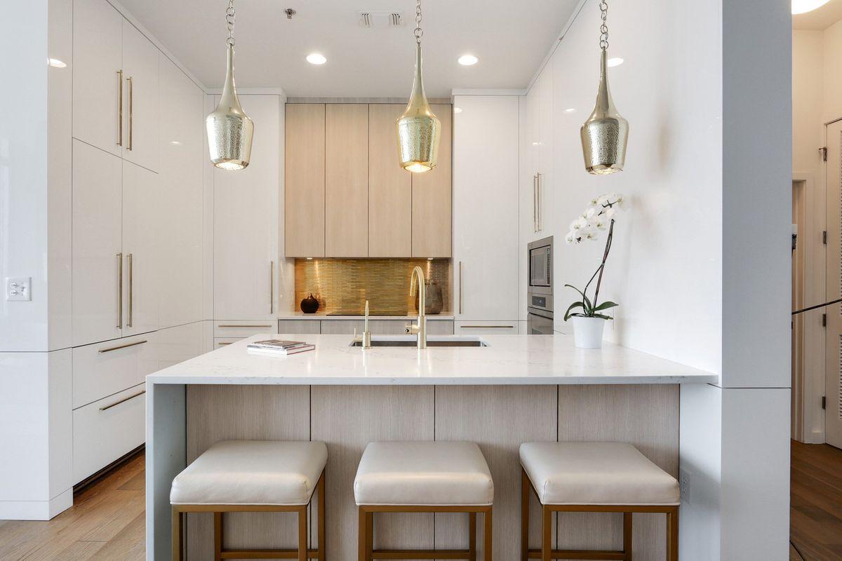 A white modern kitchen with silvery pendants.