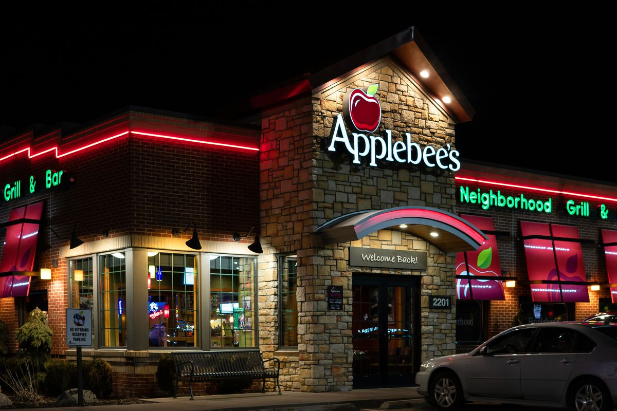 At night, the beige brick exterior of an Applebee's restaurant is illuminated by red and green neon lights