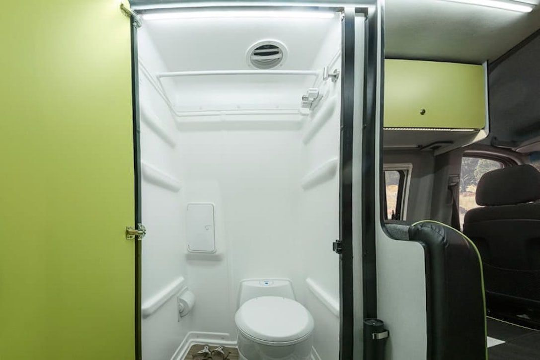 The interior of a RV camper van. There is a lime green door that is open. Inside of the small room is a toilet.