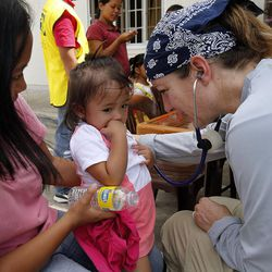 Jessica Pasturan holds her daughter Julianna Pasturan as she is checked by registered nurse Tami Asbell, Tuesday, Nov. 19, 2013 in Ormoc, Philippines.