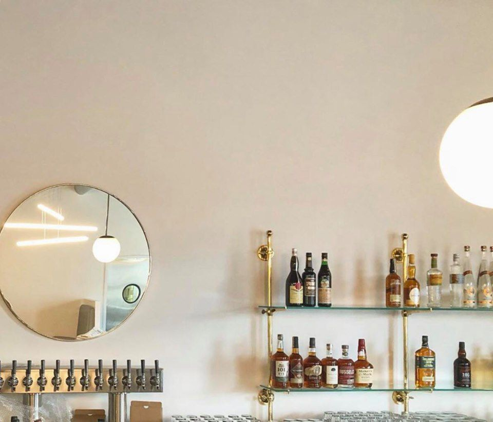 The back bar at Champagne Diner with a mirror and a row of liquor bottles.