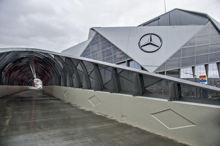 A fancy modern pedestrian bridge spanning a road near the Falcons's stadium.