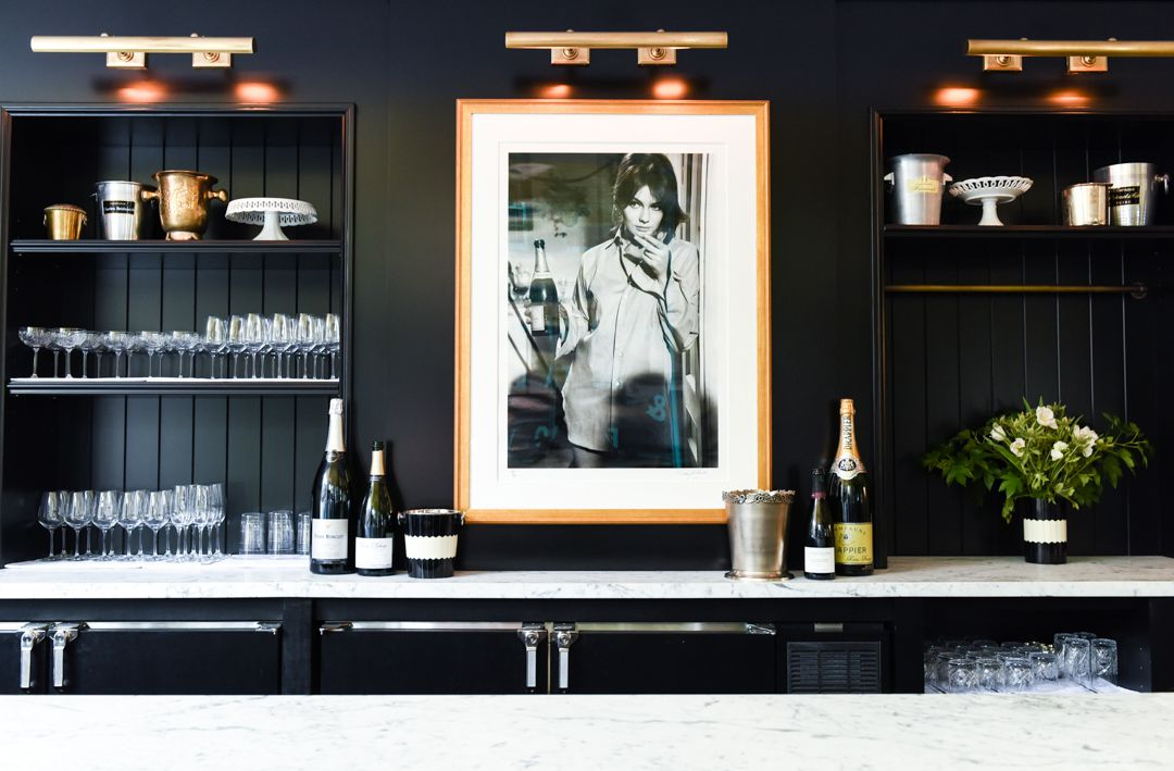 A photograph of Jacqueline Bisset hangs on a black wall