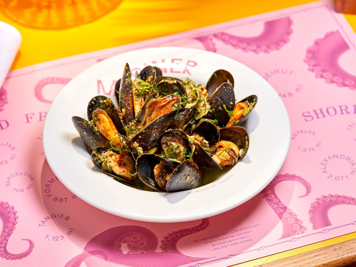 Mussels in a white dish on a pink place setting at Mo Diner
