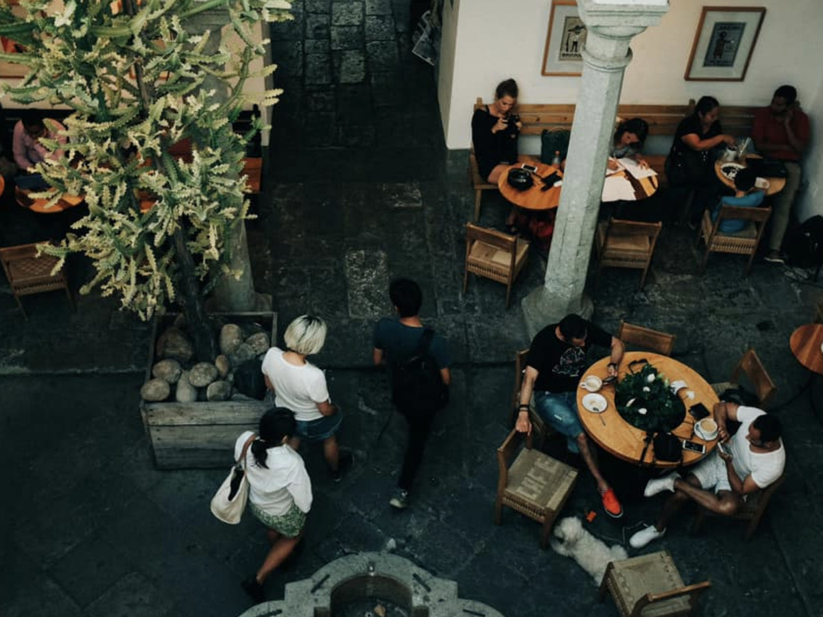 An overhead shot down into a courtyard with people drinking coffee at tables.