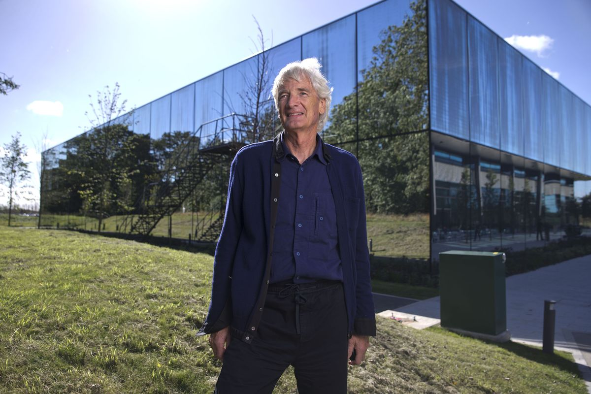 Dyson founder James Dyson stands in front of a large building.