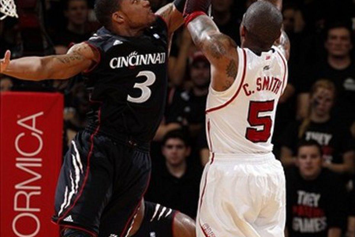 Feb 23, 2012; Cincinnati, OH, USA; Cincinnati Bearcats guard Dion Dixon (3) blocks the Louisville Cardinals guard Chris Smith (5) in the first half at the FifthThird Arena. Mandatory Credit: Frank Victores-US PRESSWIRE