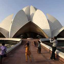 In this Wednesday, Sept. 26, 2012 photo, an Indian family takes photographs in front of the Lotus temple in New Delhi, India. India is filled with religious sites, but one of the most iconic is the Baha'i Lotus Temple, a starkly white temple in the shape of a partially blooming lotus flower. Visitors get a brief explanation of the Bahai faith and then are allowed in the inner sanctuary for quiet contemplation.