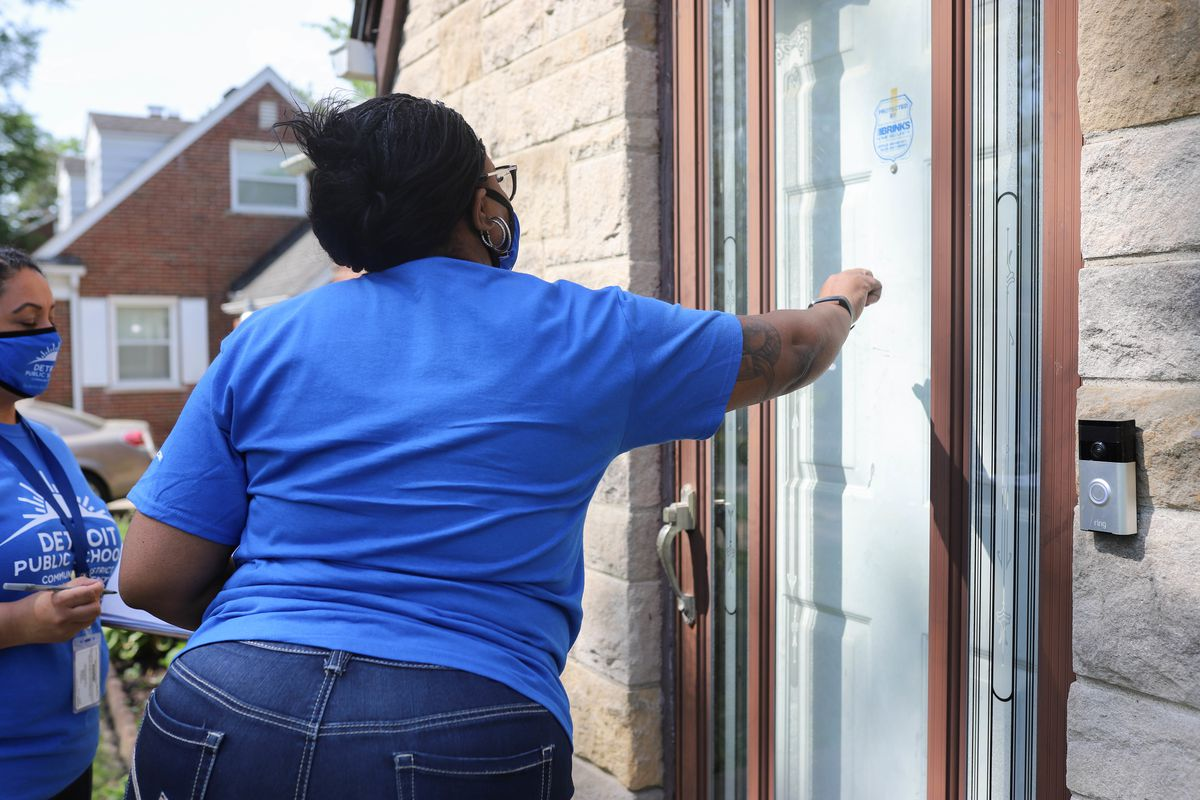 A woman wearing a blue shirt and jeans knocks on a door in Detroit, Mich., as another woman wearing a blue protective mask and blue shirt stands beside her.