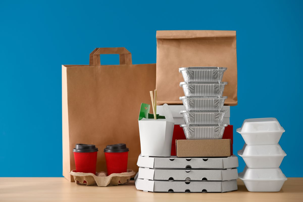Stock photograph of various types of food delivery containers piled up and arranged on a light wooden table in front of a blue background.