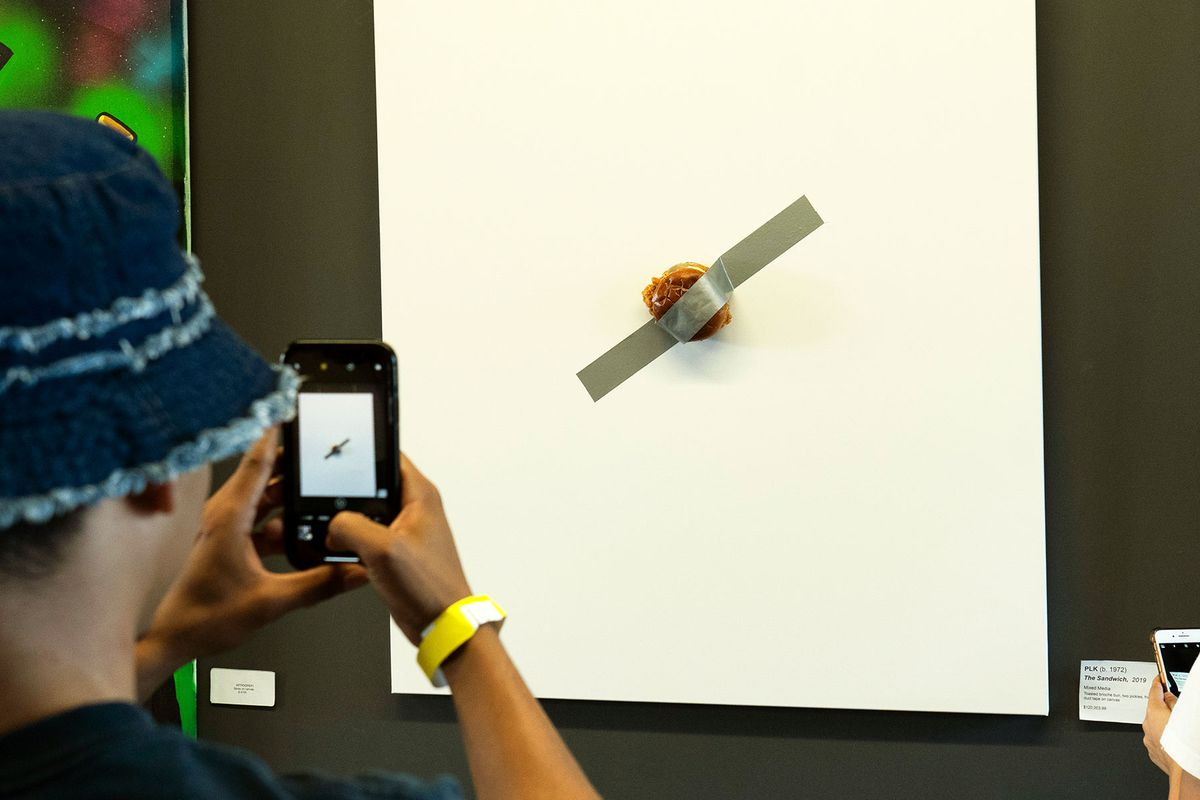 A Popeyes chicken sandwich duct taped to a canvas and exhibited at Art Basel.