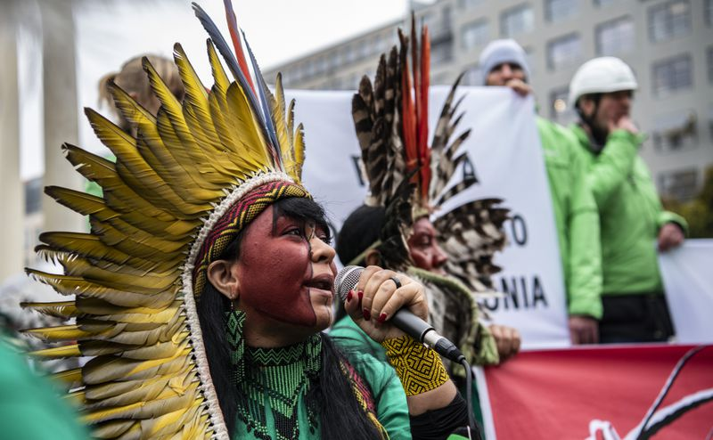 Members of an indigenous delegation from Brazil are standing in front of a hotel in Berlin, Germany.