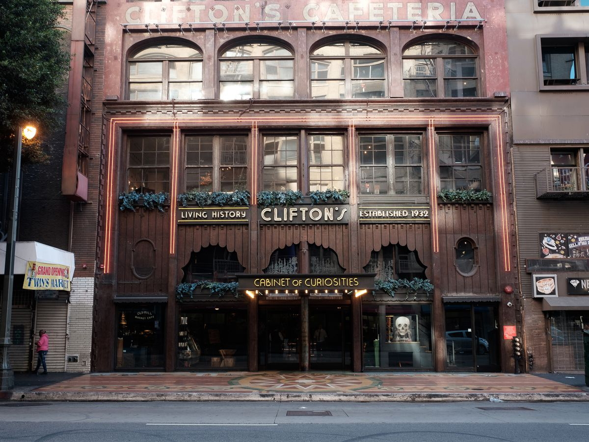 The exterior of Clifton's Cafeteria in Los Angeles. The facade is brown and red and there is a sign that reads: living history, Clifton's, established 1932, cabinet of curiosities.
