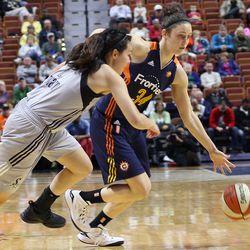 Connecticut Sun's Kelly Faris (34) drives past a San Antonio Stars' Kelsea Minato (2).