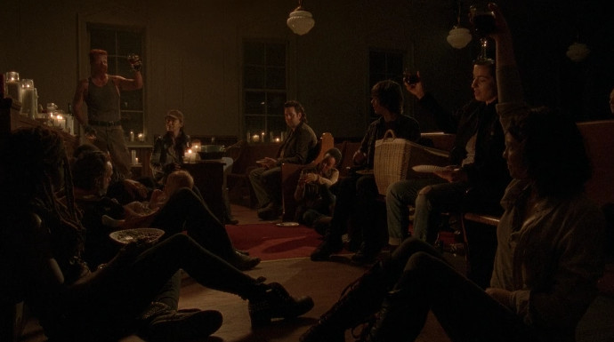 A group of people sit in a dimly lit room.