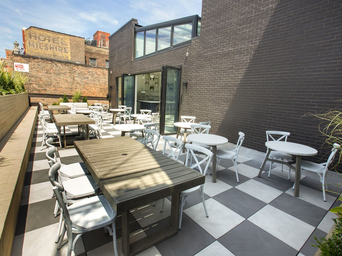 A rooftop patio dining space with a black-and-white checkerboard floor