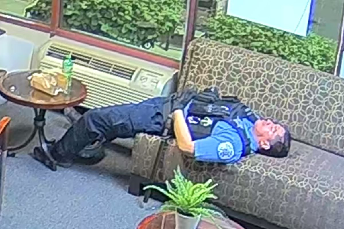A Chicago police officer on the couch in the burglarized office of U.S. Rep. Bobby Rush. Images of security video from the office were released at a news conference Thursday. In all, 13 officers can be seen, making coffee and popping popcorn at the office in an area that was beset by looting.