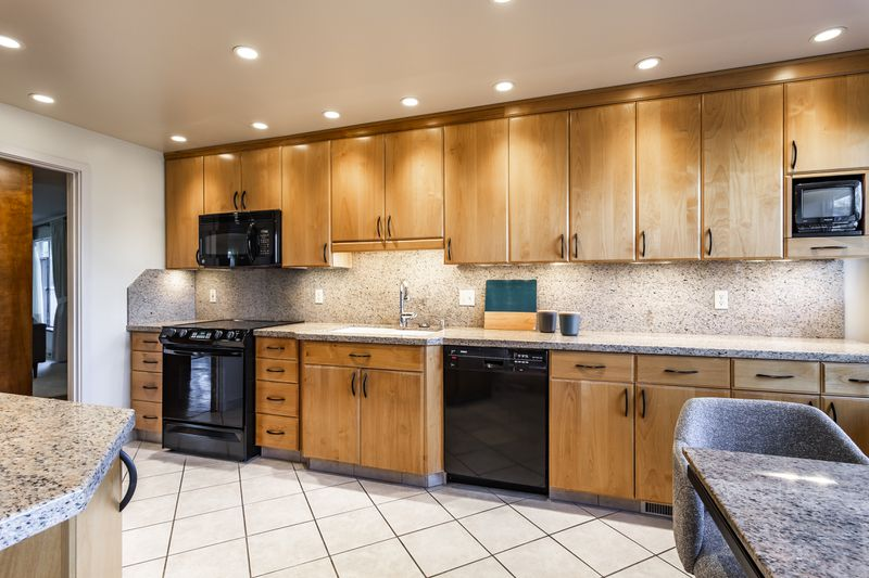 A kitchen has oak cabinets, black appliances, and speckled counter tops.