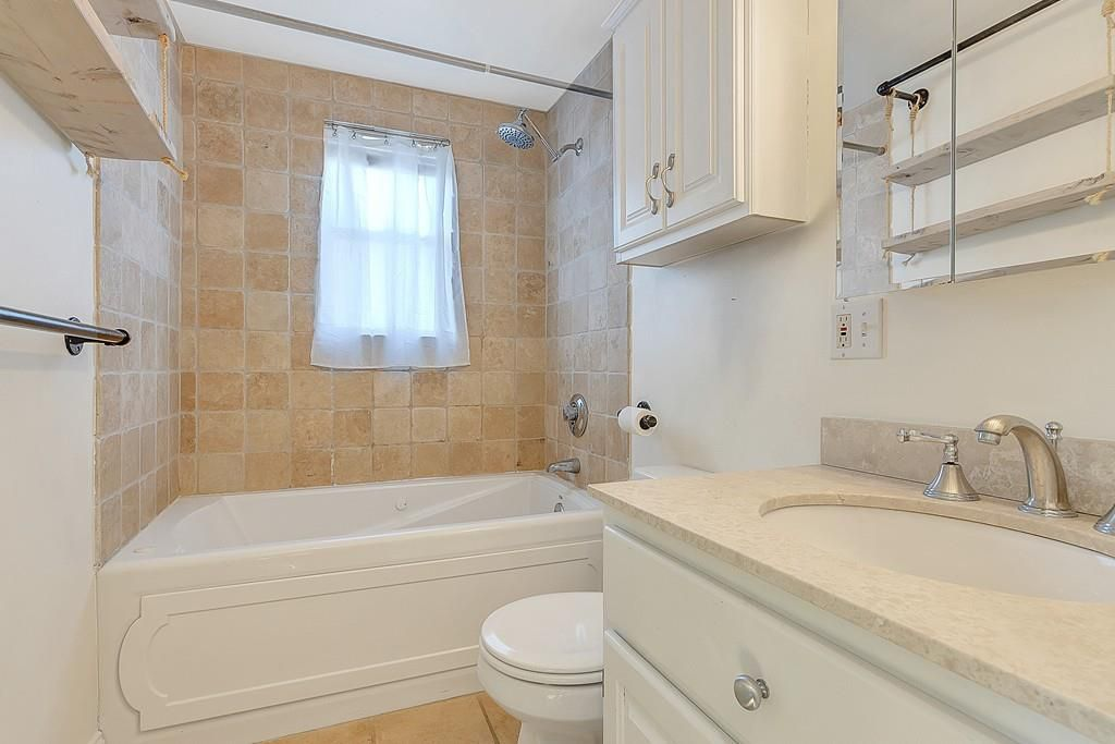 A bathroom with a vanity next to a toilet next to a shower with no curtain.