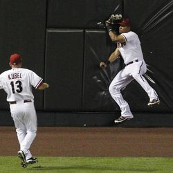 Arizona Diamondbacks' Chris Young, right, crashes into the wall while catching a fly ball hit by Pittsburgh Pirates' Pedro Alvarez as Jason Kubel (13) watches during the fourth inning of a baseball game Tuesday, April 17, 2012, in Phoenix. Young left the game after the play due to injury.