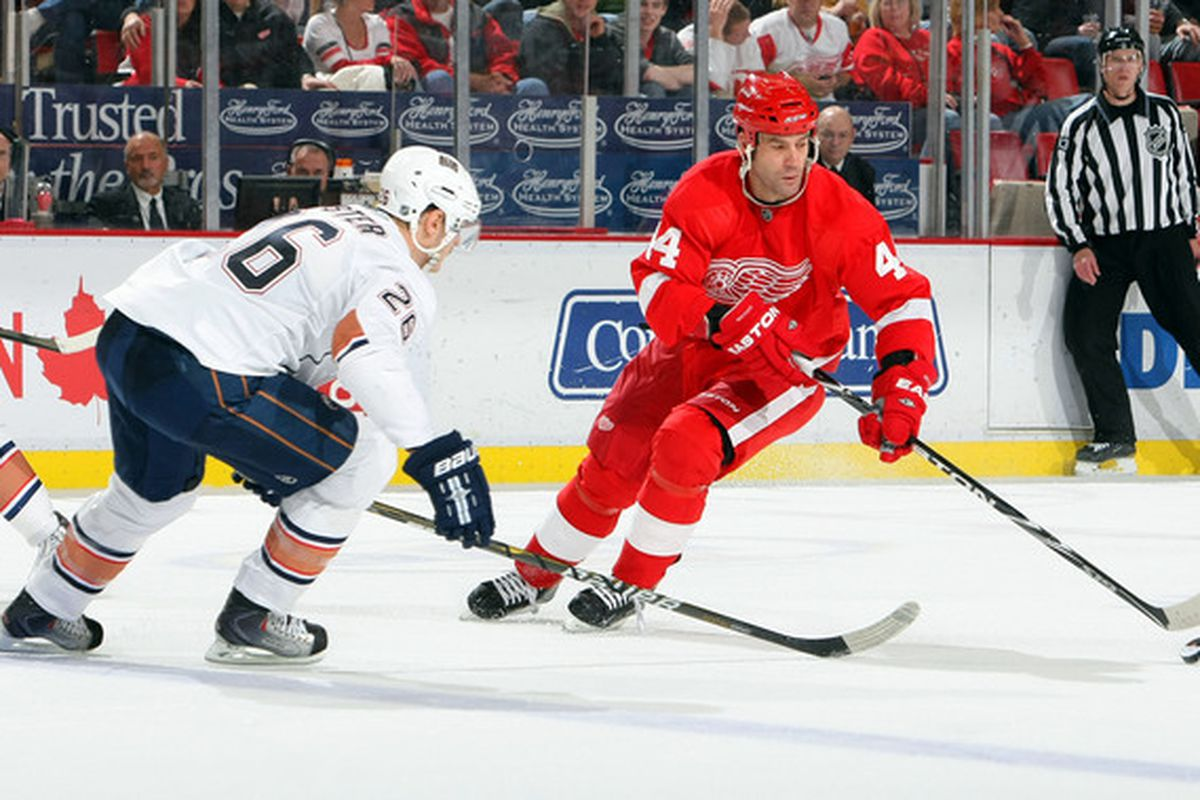 DETROIT - NOVEMBER 11:  Kurtis Foster #26 of the Edmonton Oilers defends against Todd Bertuzzi #44 of the Detroit Red Wings during their NHL game at Joe Louis Arena on November 11 2010 in Detroit Michigan. (Photo By Dave Sandford/Getty Images)