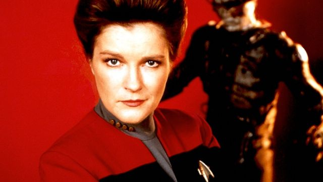 Captain Janeway stands with her arms folded in front of a Borg