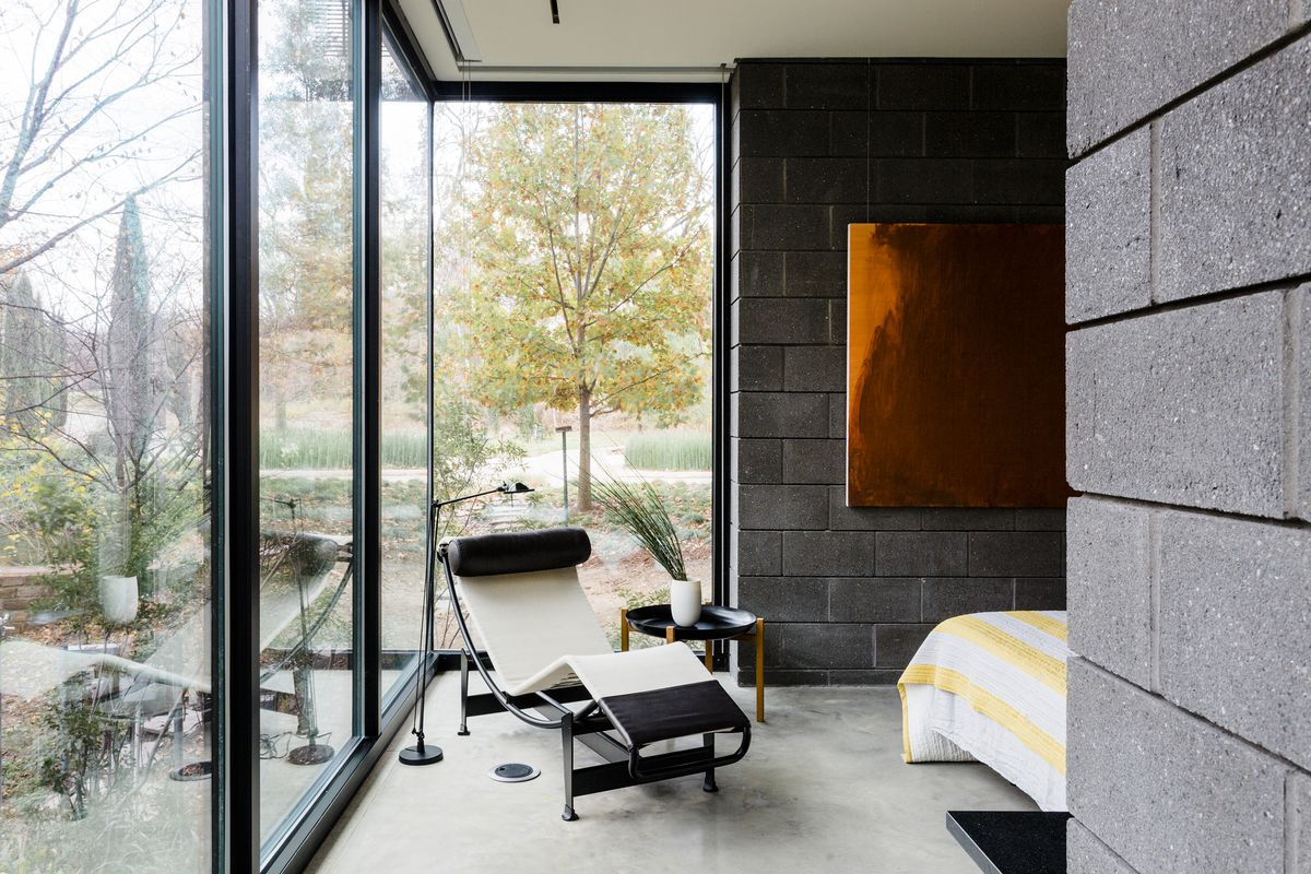 An iconic modern chaise sits in front of a corner window looking out onto the garden.
