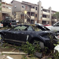 Cars and property at Portofino Apartments at Pleasant Run in Lancaster, Texas are damaged after a storm passed through the area on Tuesday, April 3, 2012. Tornadoes tore through the Dallas area Tuesday, peeling roofs off homes, tossing big-rig trucks into the air and leaving flattened tractor trailers strewn along highways and parking lots.