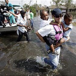 Volunteer Sarah Roberts carries flood victims to safety after they were rescued by boat from their neighborhood on the east side of New Orleans.