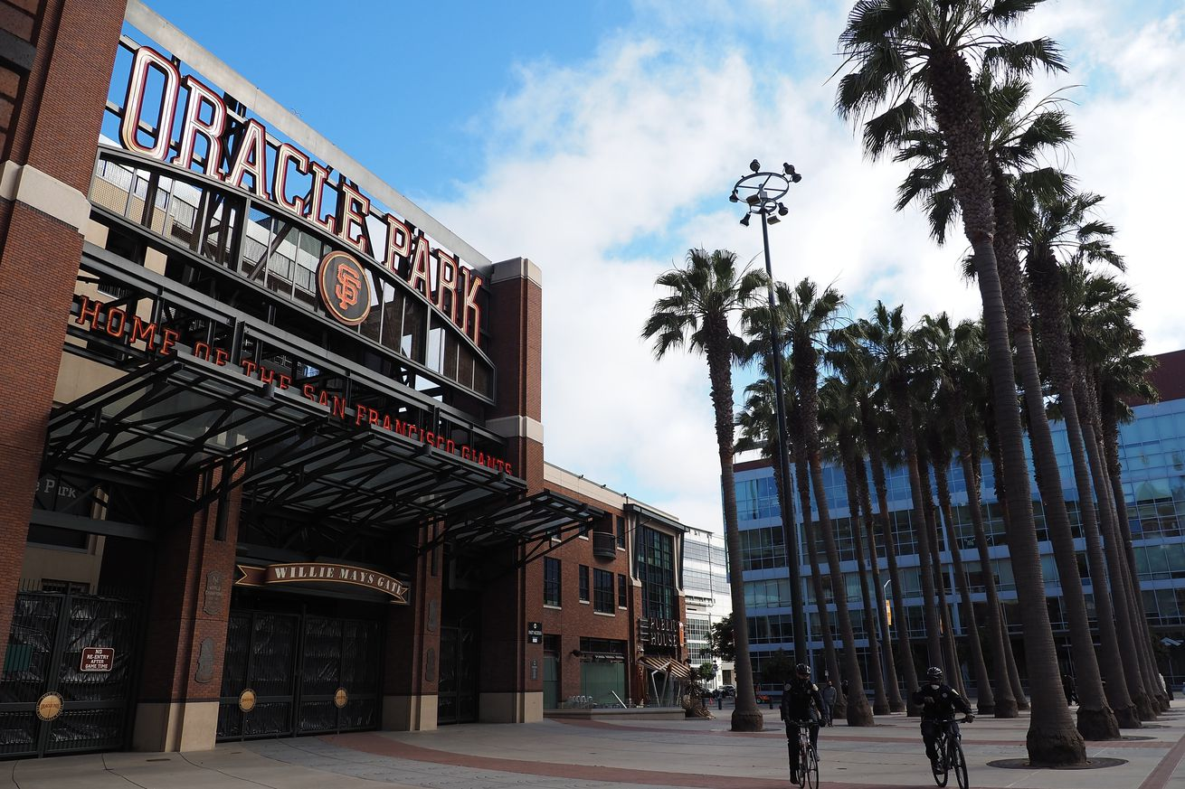 A shot of one of the entrances to Oracle Park. The entrance itself has a large sign that says Oracle Park above it and is made out of red brick. There are two rows of palm trees in front, and a partially overcast day is illuminating everything beautifully