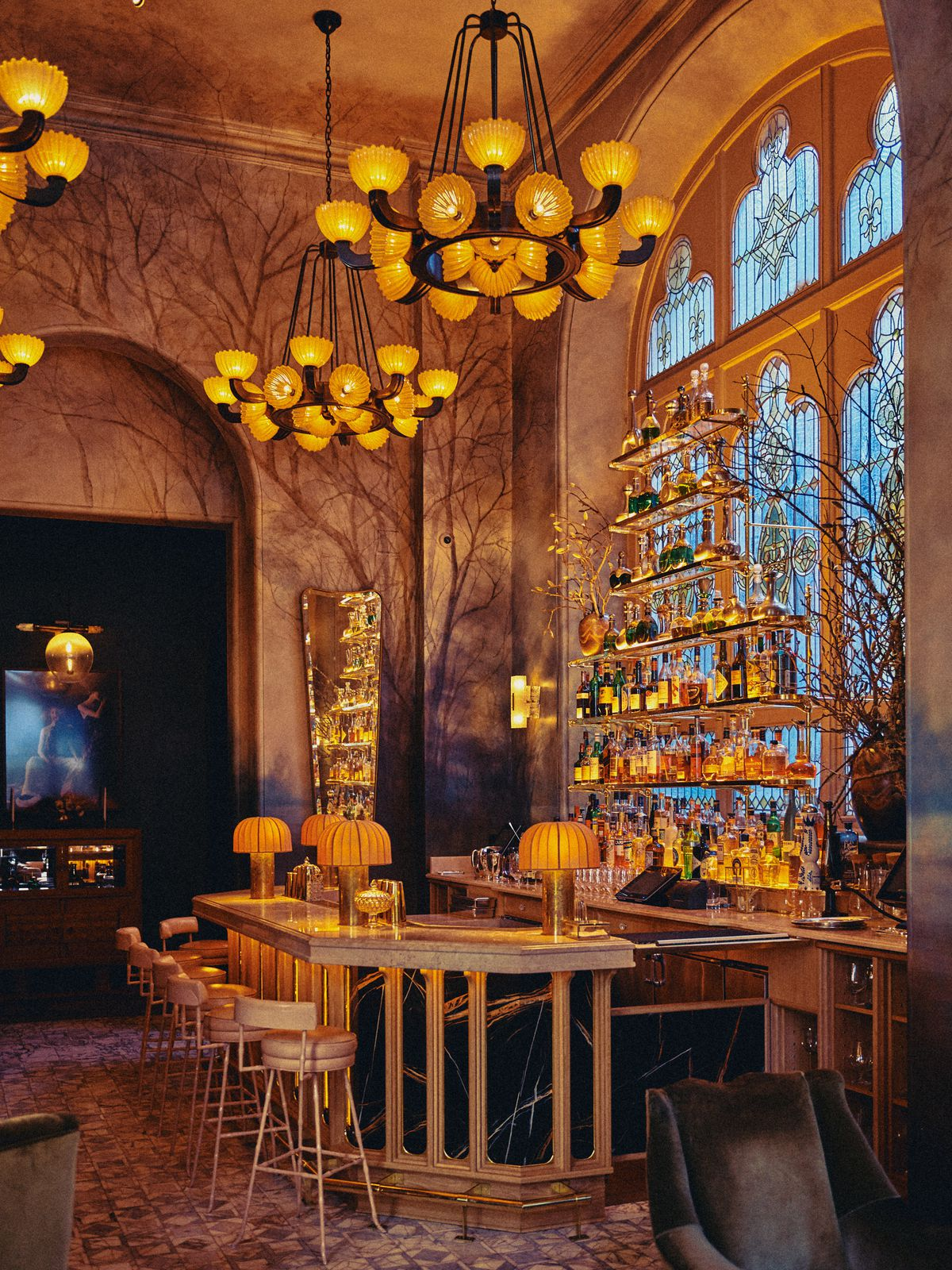 A high-ceilinged bar with chandeliers and an amber glow.