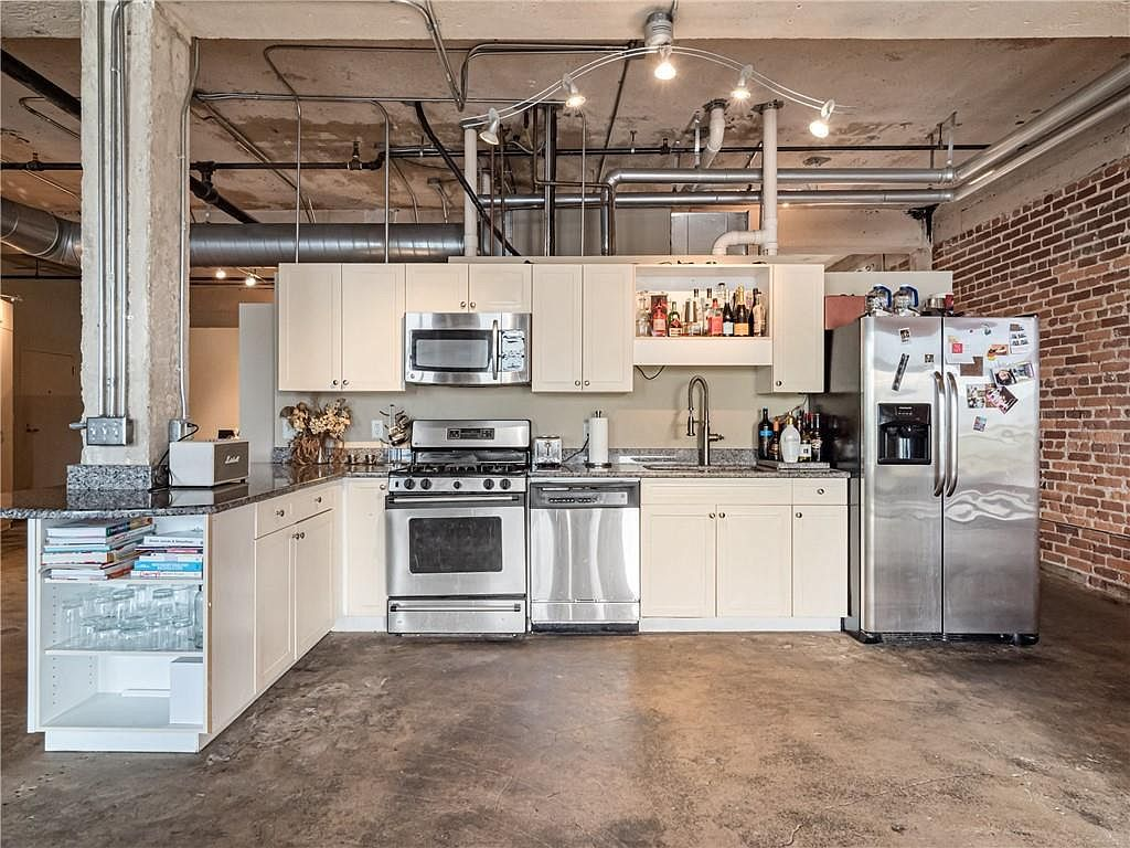 A white kitchen with a concrete floor and brick for walls.