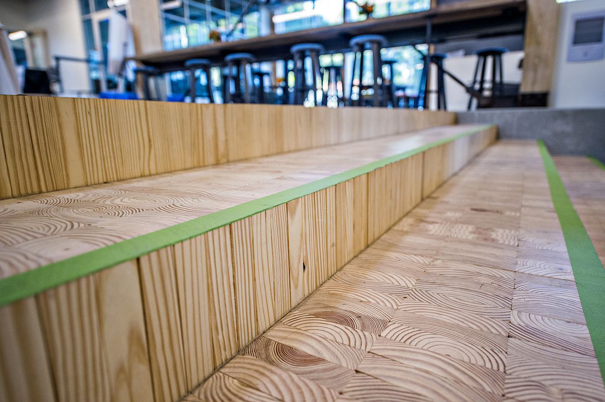 Three steps formed of boards with green tape on them for safety.