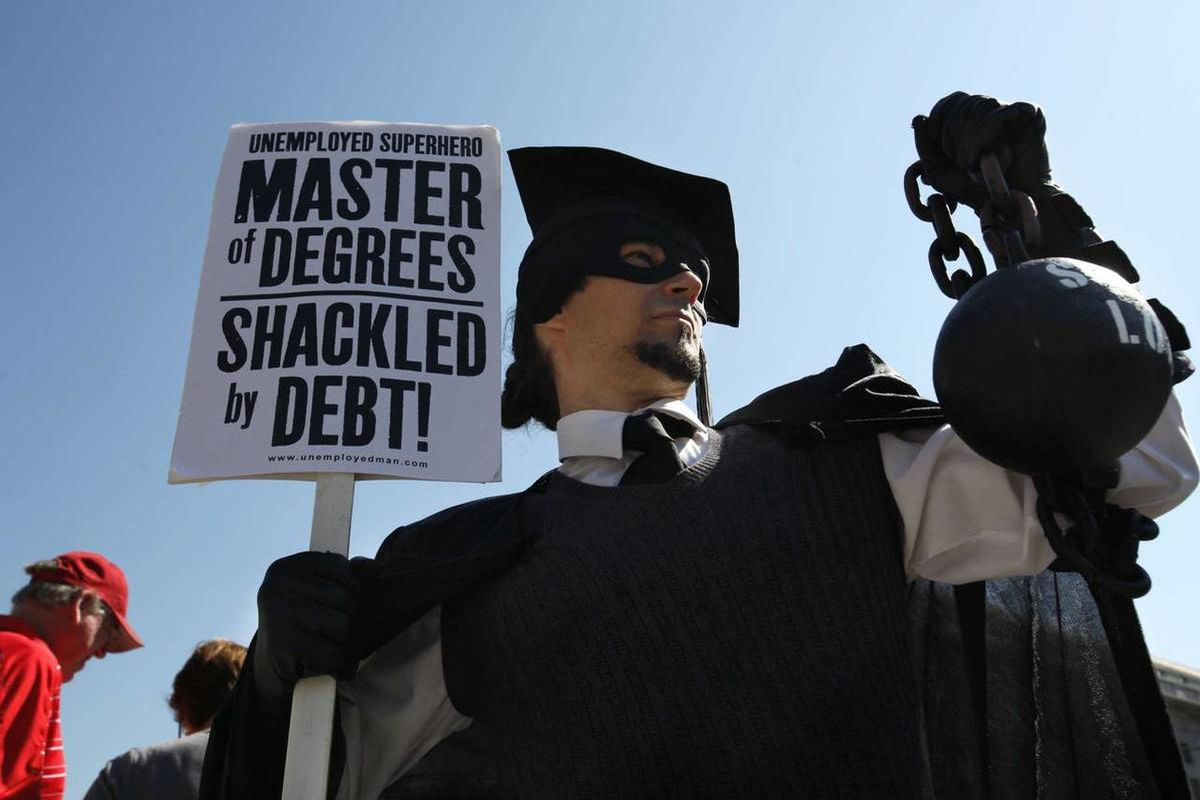 """In this Oct. 6, 2011, file photo, Gan Golan, of Los Angeles, dressed as the """"Master of Degrees,"""" holds a ball and chain representing his college loan debt, during Occupy DC activities in Washington. With college enrollment growing, student debt has stretc"""