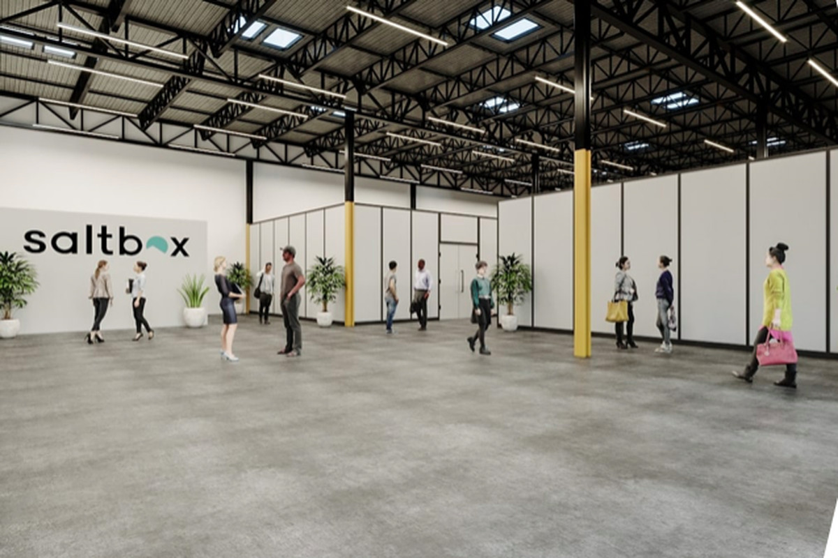 A large open warehouse space with white walls where people are working and walking around.