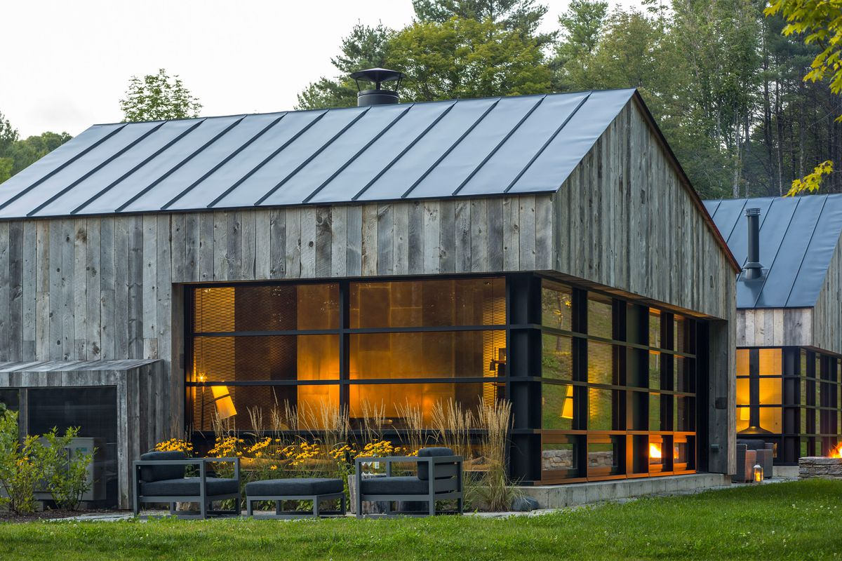 A simple, two-gabled structure clad in repurposed wood boards and generous glazing sits on a wooded site.