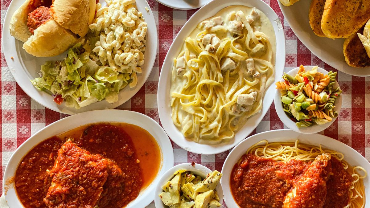 A red checkered table with Italian dishes like lasagna and chicken parm.