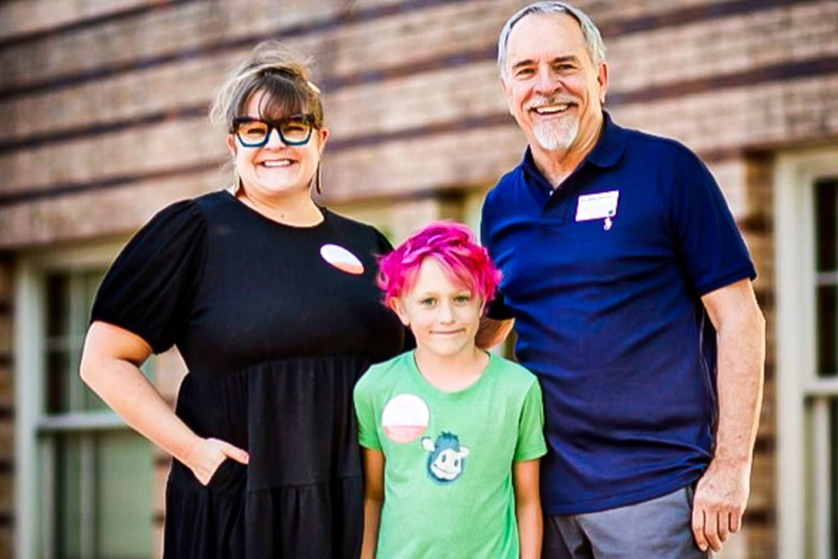 Denver school board candidate Mike DeGuire, in a blue polo shirt, stands in front of a wooden wall and windows, with his daughter, wearing a black dress, and his grandson in a lime green shirt and whose hair is dyed hot pink.