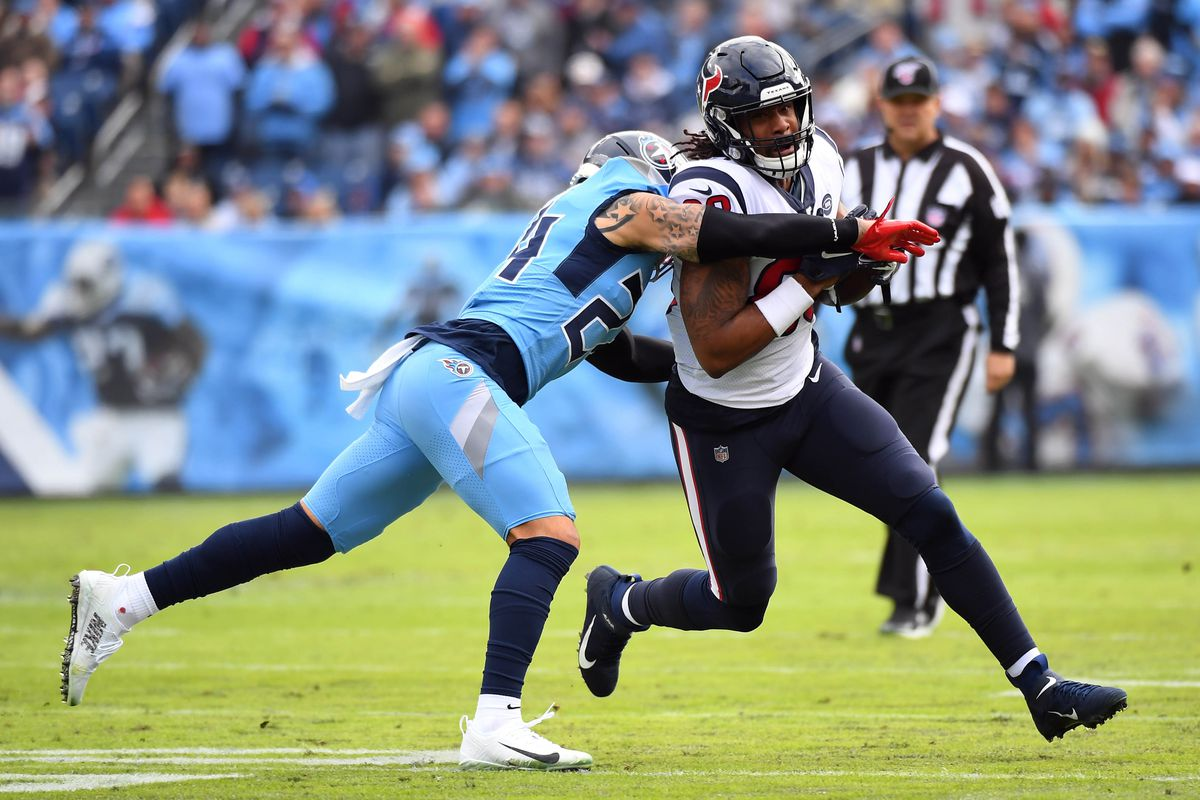 Houston Texans tight end Jordan Akins runs after a catch before being tackled by Tennessee Titans strong safety Kenny Vaccaro during the first half at Nissan Stadium