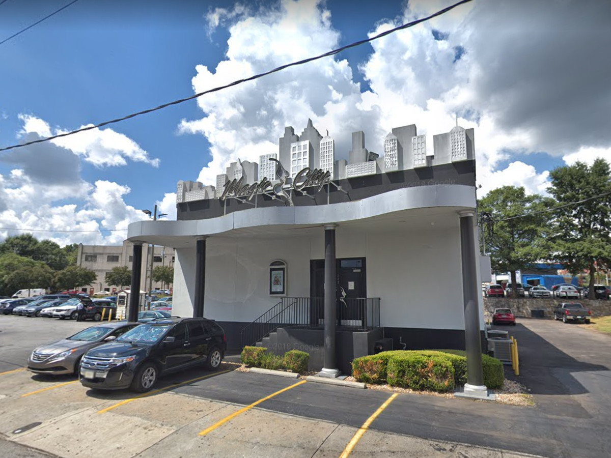 The exterior of a bar. The facade is white. There is a parking lot with a car in front of the bar.