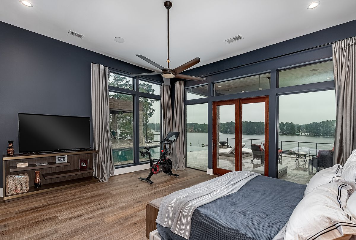 Large bedroom with gray walls and floor-to-ceiling windows overlooking a deck and lake.