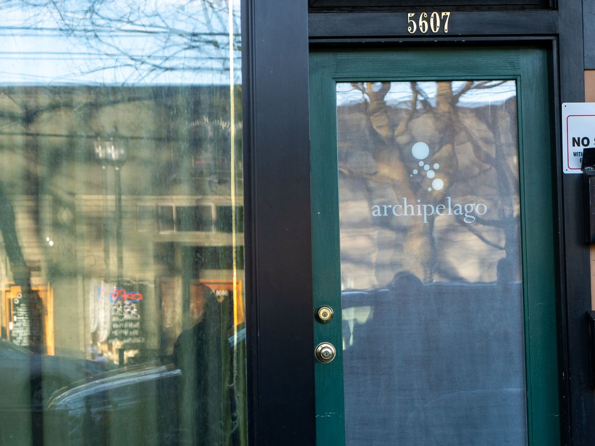 The exterior of Archipelago with the restaurant's name on the green-trimmed door.