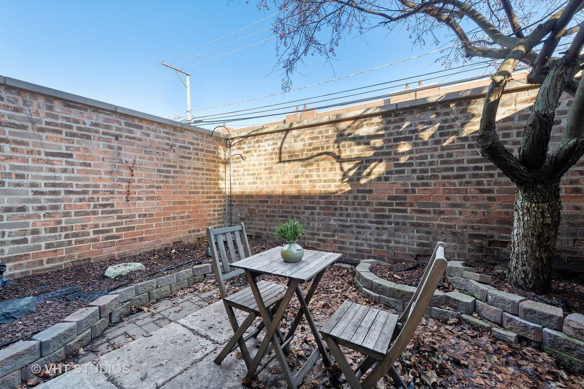 The private back patio with a mature tree, a wooden bistro set, and brick pavers.