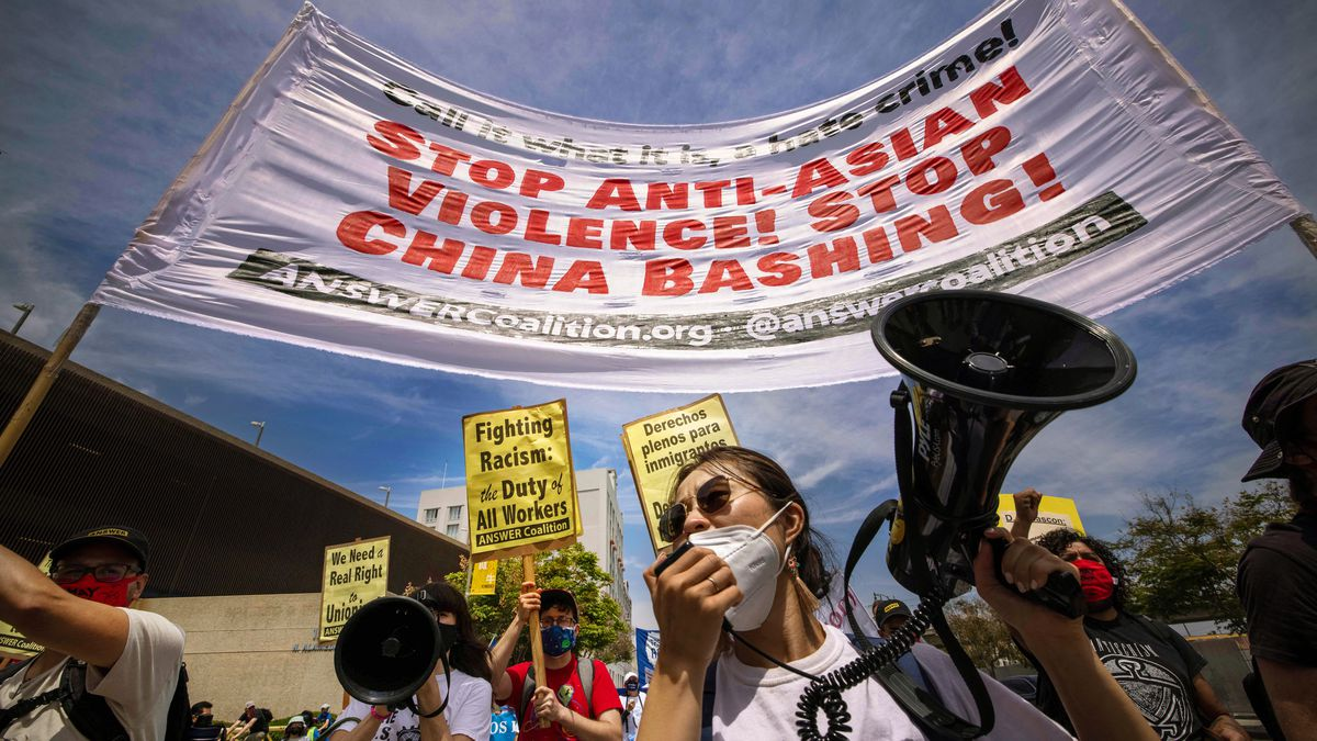 """A protester with a bullhorn stands under a banner that reads """"Stop anti-Asian violence, stop China bashing!"""""""